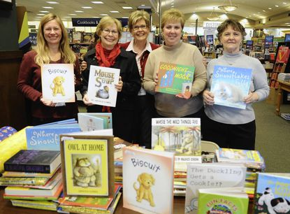 Wendy Wiessner, left, Cindy Melrose, center, Marlene Parks, second from right, and Beverly Pfingsten, right, of Barnes and Noble, hand over books collected at Barnes and Noble to Carolyn Smith, second from left, of the Empty Stocking Fund Monday.