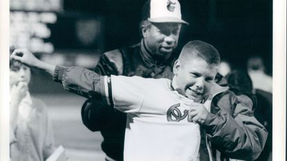 Orioles manager Frank Robinson helps 13-year-old Daryl Wise of Severna Park put on Butch Davis' jersey on Shirts Off Our Back Nights at Memorial Stadium in 1988.