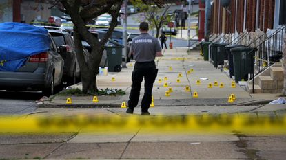 Baltimore Police crime lab recording technician Thomas Wizner stands among evidence markers where shell casings rest at the scene of a shooting in the 2200 block of Ruskin Avenue last year.