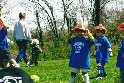 The Annapolis Soccer Club Leopards of Pal Park try field cones on their heads with the soccer balls at their feet.