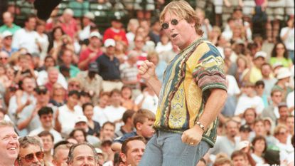 """John Denver dances atop the Orioles dugout at Camden Yards as he mouths along to his song """"Thank God I'm a Country Boy"""" on Sept. 20, 1997."""