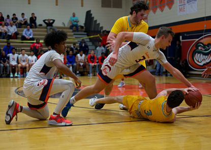 Reservoir's Ryan Saunderson (3) gets his hand on the ball as River Hill's Jackson Graves (bottom) looks for room to pass during the 3A East Region II semifinals on Tuesday, March 3.