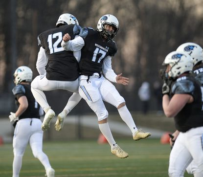 Westminster kicker Cam Doolan (17) and cousin Max Doolan celebrate after Cam made an extra point during the second half of the Owls' 21-6 win over the Lions at Western Regional Park in Woodbine Friday, March 5, 2021.