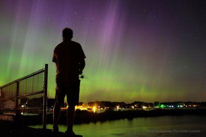 Wade Kitner looks at the aurora borealisas he fishes in Ventura, Iowa, on Tuesday, June 23, 2015.