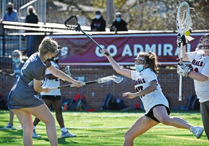 Glenelg Country's Kate Fuhrman, from left, shoots past Severn's Hailey Stewart to score against goalie Arielle Hillock in the second half of girls lacrosse game on Mar. 29, 2021.