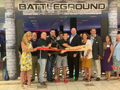 Battlegorund owners in the middle cutting the ribbon at their grand opening, wearing black polos (from left to right): Mike Borris, Anthony DeJesus and John Wah. - Original Credit: Courtesy Photo