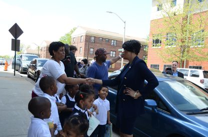 Baltimore Mayor Stephanie Rawlings-Blake greets people on Presstman Street in Sandtown-Winchester after speaking with reporters at the New Song Academy.