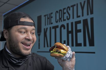 Restaurant owner Raymon Simpson with his All-American Turkey Burger at Crestlyn Kitchen.