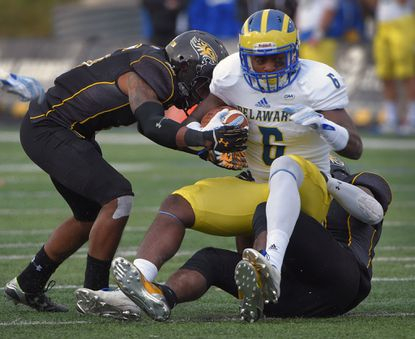 Towson Tigers defensive back Troy Jeter (6) assists cornerback Niquekko Cook (below) who wraps up Delaware Fightin' Blue Hens wide receiver Jamie Jarmon (6) during a key CAA matchup at Unitas Stadium. The Tigers blanked Delaware, 19-0.