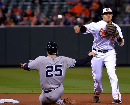 Baltimore Orioles shortstop Manny Machado looks over New York Yankees' Mark Texeira as he rears back to throw over to first base for a double play, hit by batter Carlos Beltran at Oriole Park at Camden Yards.