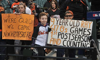Young Orioles fans show off signs they brought to the team's first playoff game at Camden Yards since 1997.