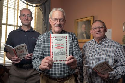 Chad Merrill, weather prognosticator, Chad Fisher, editor and direct descendant of founder John Gruber, and Jerry Spessard, business manager, right, each hold a copy of the Hagers-town Town and Country Almanack, just released for 2021.