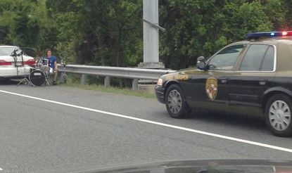 An unidentified man who ran out of gas set up a drum kit as he awaited assistance on Interstate 695.