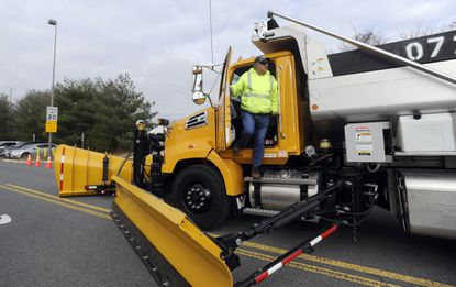 Doug Kidd, a team leader with the Maryland State Highway Administration, climbs out of the state's newest snow plow, which is a double wing truck that can plow two lanes at one time due to its 24-foot wing span. It was on display at the Maryland State Highway Administration's statewide operations center.
