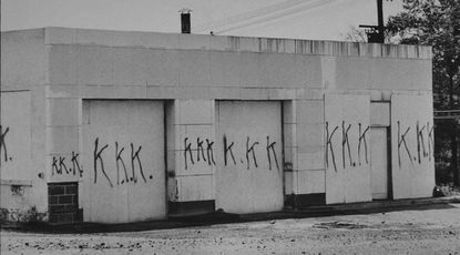 An abandoned gas station near the Phillips 66 station operated by Francis Raymond Edwards on July 22, 1967, is covered in graffiti representing the Ku Klux Klan.