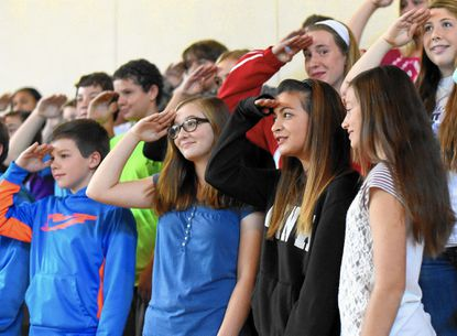 New Windsor Middle School eighth graders, from left, Tate Bittner, Alex See, Emalie Venters, and Tiffany Green salute after singing a song thanking veterans for their service during a Veterans Day ceremony Tuesday, Nov. 11 in New Windsor.
