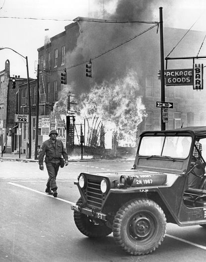 National Guardsman, Sidney Katz, on Caroline and Eden Streets during the burning of a local shop.