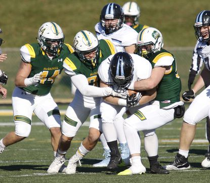 McDaniel's Christian Hauffman and Kai Leibfried stop Johns Hopkins Luke Yakley during a 2019 football game at Gill Stadium in Westminster.