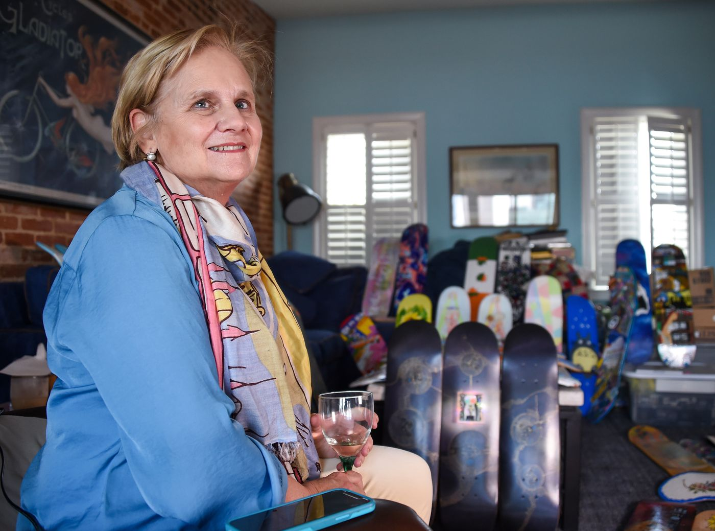 Cindy Conklin sits in her living room with painted skateboard decks on Wednesday, April 7, 2021; they'll be auctioned off to help fund the completion of Jake's Skate Park at Rash Field.
