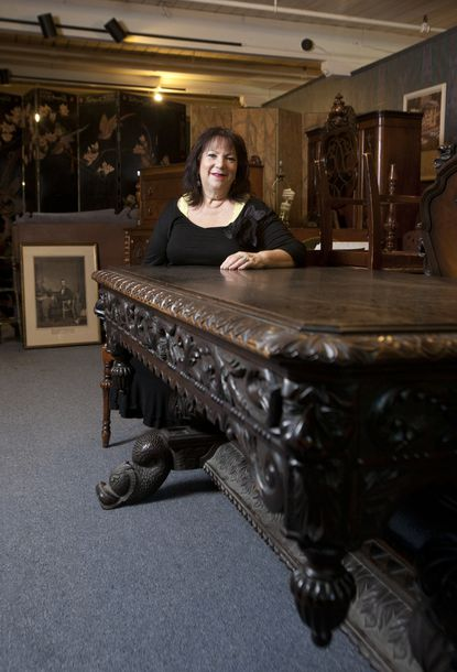 Shelley Harris, co-owner of Caplan's Auction & Appraisal Co., shows off furniture to be auctioned.