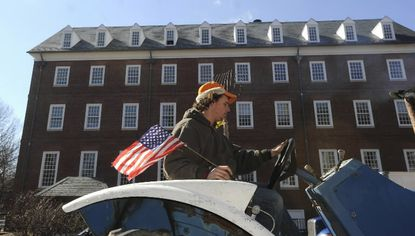 Christopher Pfefferkorn, a farmer from West Friendship in Howard County, drives his tractor along Rowe Blvd near the State House. Tractors from several counties came to Annapolis to support SB 391, which would repeal the septic limits law which was passed last year.