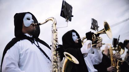 Dressed as the Phantom of the Opera, saxophonist Jon Locke, left, and mellophonist Garrett Stair warm up with the Winters Mill High School marching band before the Westminster Halloween Parade in 2010.
