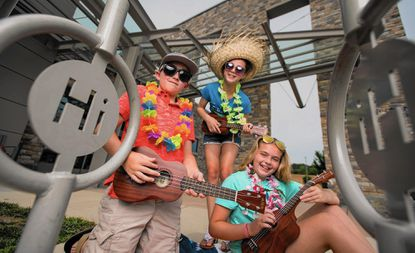 From left, TC Goodman, Lauren Roselle and Jane Goodman try out the library's new lending ukuleles