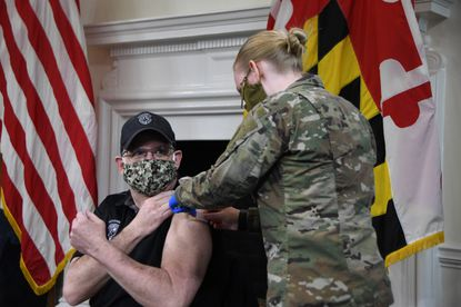 """Maryland Gov. Larry Hogan gets a bandage placed on his arm by a member of the Maryland National Guard after receiving the first dose of the Moderna coronavirus vaccine at the State House in Annapolis on Monday, Jan. 18, 2021. """"I really did not even feel the needle go in,"""" he said later. (Pamela Wood/Baltimore Sun)."""