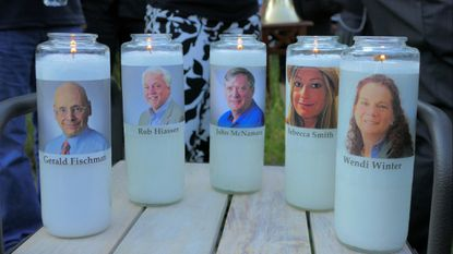 Candles honoring Gerald Fischman, Rob Hiassen, John McNamara, Rebecca Smith, and Wendi Winters during a candlelight vigil last year for. the five Capital Gazette employees slain during a shooting spree in their newsroom.