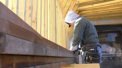 "A construction worker for Greenleaf Remodeling works on a house in the film ""The Tradesmen: Making an Art of Work."""