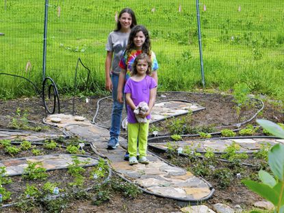 Sisters , from back to front, Maggie, 11, Ava, 10 and Lucia, 6, Possidente have worked for more than a year to create a butterfly garden at Oregon Ridge Park. They used all native plants and set them around a butterfly-shaped site.