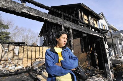 Sherry Strothers stands outside her home that burned in a fire over a week ago.
