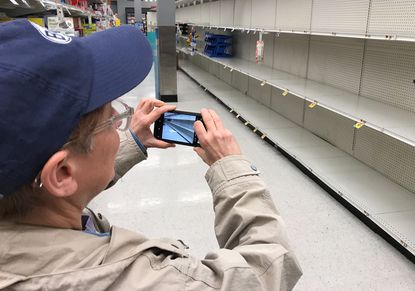 Stephanie Gibson of Ednor Gardens paused Friday afternoon to photograph the empty shelves that usually hold toilet paper and paper towels at the Giant at York Road Plaza.