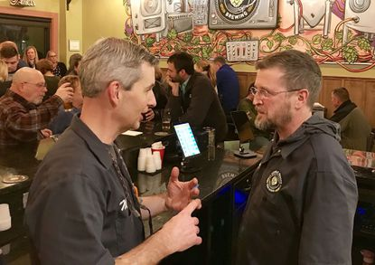 Mark Moody, left, and Craig Willig, co-owners of Double Groove Brewing in Forest Hill, chat briefly while their craft brewery is packed with customers Friday, Jan. 24. A mural created by Baltimore-area artist Marshall Adams is on the far wall.