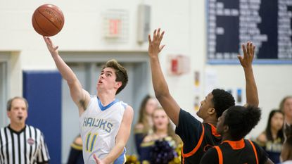 River Hill boys basketball senior Luke Champion, left, lays the ball up during the Hawks' 60-56 win over Oakland Mills in the 2A South, Section I final on Feb. 28.
