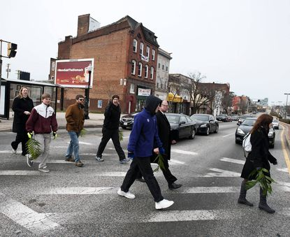 A procession of clergy and congregants from the Cathedral of the Incarnation walks across North Avenue with palm fonds on Palm Sunday. The contingent was walking back to the cathedral in Charles Village after joining the 10th annual Blessing of the City outside City Hall on Sunday morning.