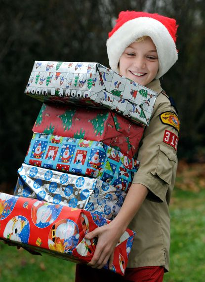 Will Kirkpatrick, 11, of Boy Scout Troop 319, which meets at Hunt's Memorial United Methodist Church, carries gifts set for disadvantaged children.