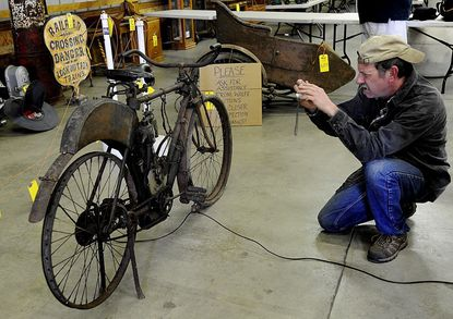 Brian Rooney, of Lovettsville, Va., photographs a 1903 Indian Motocycle that will be auctioned Saturday at the Frederick Fairgrounds. The motorcycle is believed to be one of the oldest unrestored American-manufactured motorcycles in existence.
