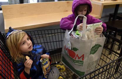 Axel Bruno, left, 3, and his sister Tilly Bruno, 7, have a snack duringthe grand opening of Mom's Organic Market in the Rotunda last year. The owner of the market says rich people like himself should take on more of the tax burden.