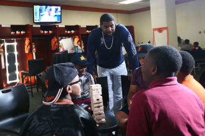 Orioles relief pitcher Mychal Givens interacts with kids in the team's clubhouse during Players' Weekend activities.