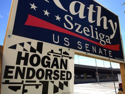 A sign touting Gov. Larry Hogan's endorsement is attached to a campaign sign for Republican U.S. Senate candidate Kathy Szeliga.