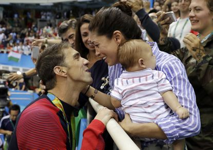 """Michael Phelps celebrates winning his gold medal in the men's 200-meter butterfly with his fiance Nicole Johnson and baby Boomer during the swimming competitions at the 2016 Summer Olympics in Rio de Janeiro, Brazil. Phelps says he has """"no desire"""" to return to competitive swimming, but he's eager to stay involved with the sport and cheer on those who follow in his enormous wake."""