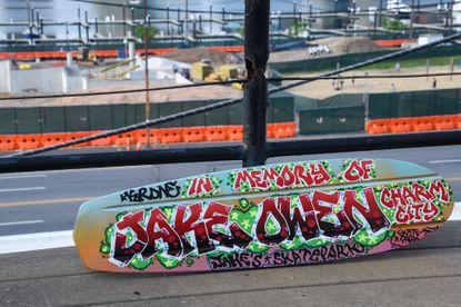 """""""In Memory of Jake Owen"""" is painted on a skateboard deck at the home of Cindy Conklin on Wednesday, April 7, 2021; the board will be auctioned off to help fund the completion of Jake's Skate Park at Rash Field, which is seen in the background."""