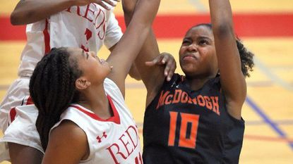 McDonogh's Sijay Matsinye is fouled on a shot in the second half as she is defended by Roland Park's Ja' Niah Henson and Christyn Robinson.