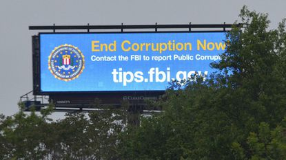 An FBI advertisement on an electronic billboard in Baltimore City solicits tips about public corruption.