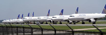 United Airlines planes are parked at George Bush Intercontinental Airport Wednesday, March 25, 2020. The airlines have reduced the number of flights flown each day as fewer people are flying due to the COVID-19 outbreak. The new coronavirus causes mild or moderate symptoms for most people, but for some, especially older adults and people with existing health problems, it can cause more severe illness or death. (AP Photo/David J. Phillip)