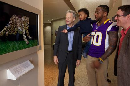 Erin Henderson and his 2-year-old son learn about big cats during a visit to National Geographic's D.C. offices.