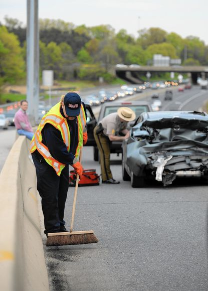 John Kohl, a member of the Catonsville Fire Department since 1988, helps clean up the site of an accident on Interstate 95 on May 1, his last day of service to the county.
