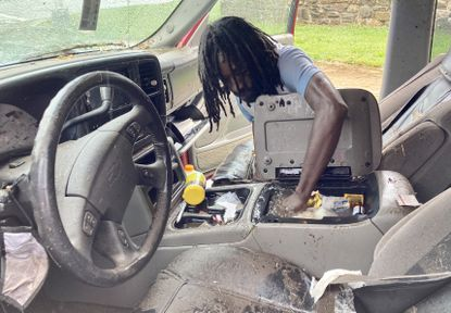 Jason Thomas of Baltimore fishes through his flooded console box after getting stranded in high water that had reached the windows of his Chevy Tahoe on Hillen Road at E. 35th St. He was able to get out of his car, but can't get it started again. The water receded when firefighters cleared the nearby sewage drains.