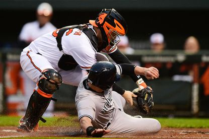 Jacoby Ellsbury of the New York Yankees, right, is tagged out at home plate by Orioles catcher Caleb Joseph in the first inning at Oriole Park at Camden Yards on May 4, 2016 in Baltimore.